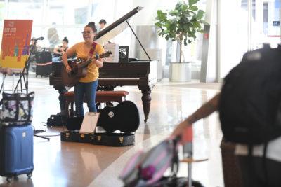 Socorra playing guitar at Airport