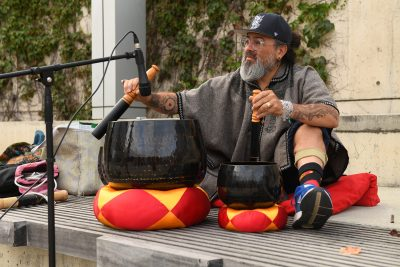 Musician playing musical bowls on a cushion out in City Hall plaza