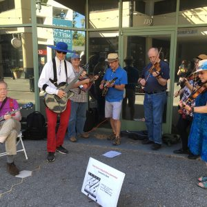 Seven piece fiddler group performing outside downtown business.