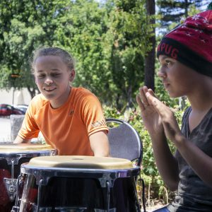 Two teens drumming outside on conga drums