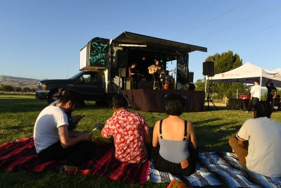 People on picnic blanket watching band on the San Jose Jazz Boom Box stage--a truck that folds out into a stage.