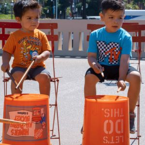 Two children playing on the bucket drums.