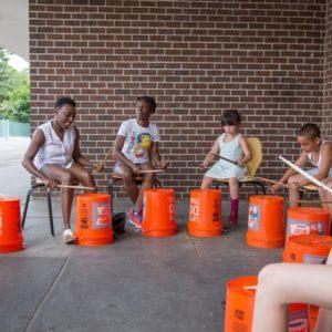 Kirk Woodard leads bucket drumming with a few tiny volunteers.