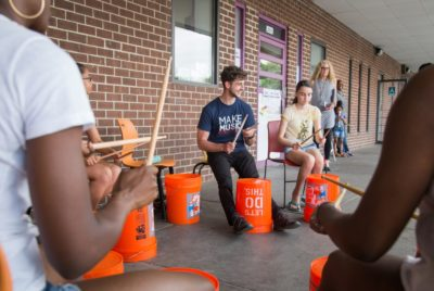 Volunteers are participating in a Make Music Hartford bucket drumming circle.