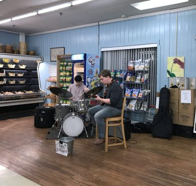 Duo of jazz musicians performing inside a food market on drums and guitar