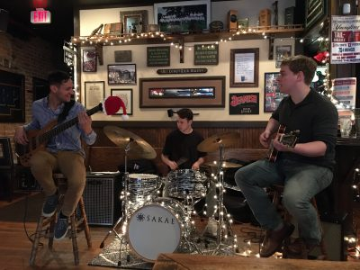 Trio of jazz musicians performing in a pub on bass guitar, drums and guitar